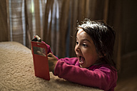 Little girl playing with smartphone at home - JASF01564