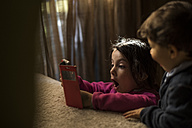 Little girl playing with smartphone while brother watching her - JASF01570