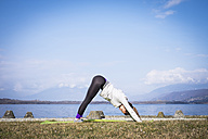 Woman practicing yoga at a lake - SIPF01460