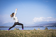 Woman practicing yoga at a lake - SIPF01463