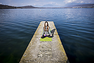 Woman practicing yoga on a pier at a lake - SIPF01472