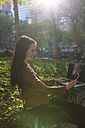 USA, New York, Manhattan, smiling young businesswoman sitting at table in a park looking at cell phone - BOYF00692