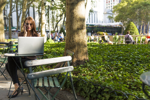 USA, New York, Manhattan, young businesswoman on the phone sitting at table in a park with laptop - BOYF00698