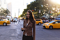 USA, New York, Manhattan, smiling young businesswoman with tablet on the street - BOYF00713