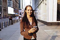 USA, New York, Manhattan, smiling young businesswoman looking at cell phone - BOYF00719