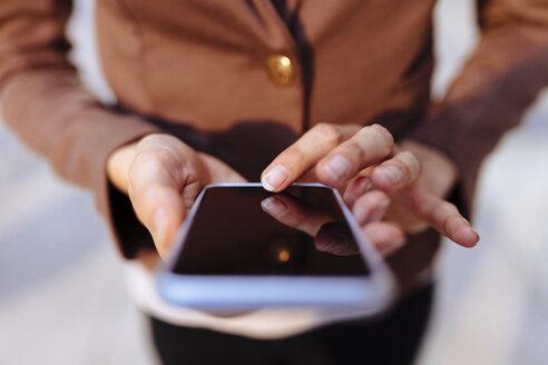 Businesswoman using cell phone, close-up - BOYF00725