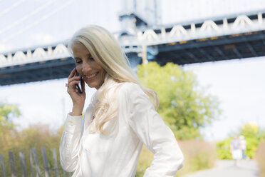 USA, Brooklyn, smiling mature woman on the phone in front of Manhattan Bridge - GIOF02290