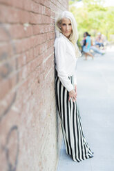 Portrait of mature woman leaning against brick wall - GIOF02293