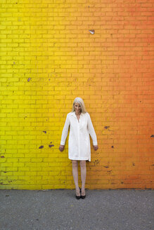 Smiling woman wearing white shirt blouse standing in front of orange wall - GIOF02299