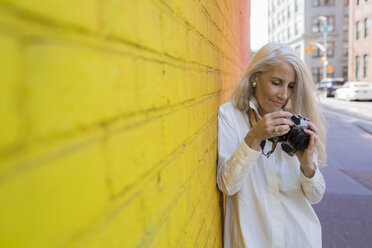 Mature woman with camera leaning against wall - GIOF02302