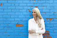 Smiling mature woman standing in front of light blue wall - GIOF02305