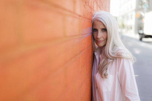 Portrait of mature woman leaning against orange wall - GIOF02308