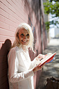 Portrait of smiling businesswoman  with personal organizer - GIOF02314