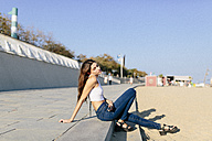 Young woman relaxing on beach promenade at sunset - GIOF02330