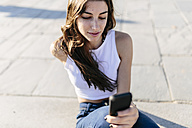 Young woman relaxing on beach promenade looking at cell phone - GIOF02333