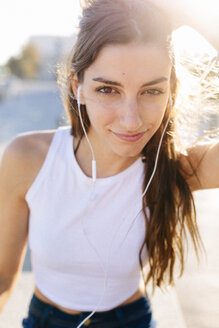 Portrait of smiling young woman with earphones at sunset - GIOF02336