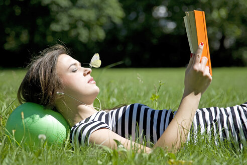 Woman with earphones lying on a meadow reading a book - KLR00516