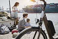 Germany, Hamburg, family having a break from a bicycle tour at River Elbe watching a container ship - RORF00684