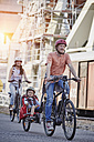 Germany, Hamburg, family riding e-bikes at the harbor - RORF00696