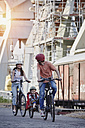 Germany, Hamburg, family riding e-bikes at the harbor - RORF00699