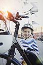 Portrait of smiling girl wearing helmet next to bicycle - RORF00702
