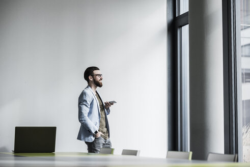 Young businessman standing in office, using smart phone - UUF10148