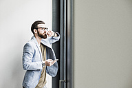 Young businessman standing in office, using smart phone - UUF10151
