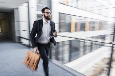 Businessman running in corridor of an office building - UUF10178