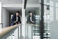 Businessman standing in office building, using digital tablet - UUF10181