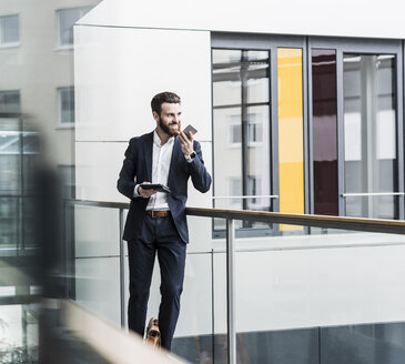 Businessman standing in office building, using smart phone and digital tablet - UUF10184