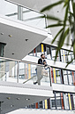 Businessman standing on landing of an office building, talking on the phone - UUF10187
