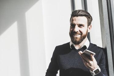 Businessman holding smart phone, talking - UUF10193