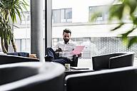 Businessman sitting in lobby, drinking coffee, reading documents - UUF10196