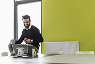 Young businessman sitting in office using mobile devices - UUF10202