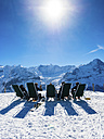 Switzerland, Canton of Bern, Grindelwald, view from First to Wetterhorn and Eiger, skiers sitting on deckchairs in the sun - AM05353