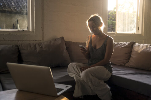 Blond woman sitting on the couch at backlight looking at cell phone - KNTF00813