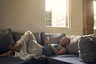 Smiling woman lying on the couch using cell phone - KNTF00816