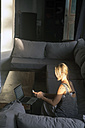 Blond woman sitting on the couch at sunlight using cell phone - KNTF00819