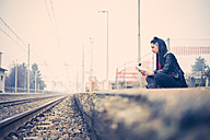 Dark-haired young woman sitting on platform reading a book - SIPF01486