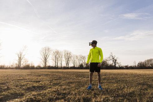 Athlete wearing VR glasses in rural landscape - UUF10213