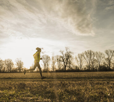 Man running in rural landscape at sunset - UUF10225