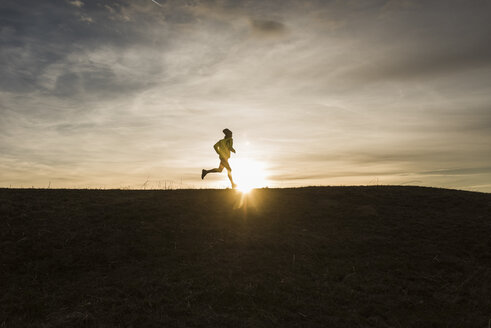 Man running in rural landscape at sunset - UUF10228