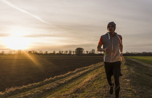 Man running in rural landscape at sunset - UUF10231