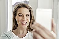 Happy woman taking a selfie - FMKF03598