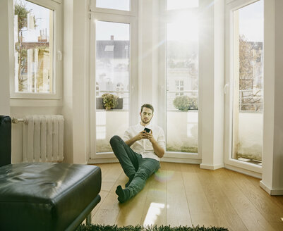 Man sitting on floor looking at cell phone - FMKF03601