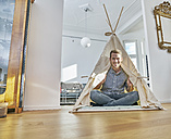 Smiling man sitting on floor in a teepee - FMKF03607