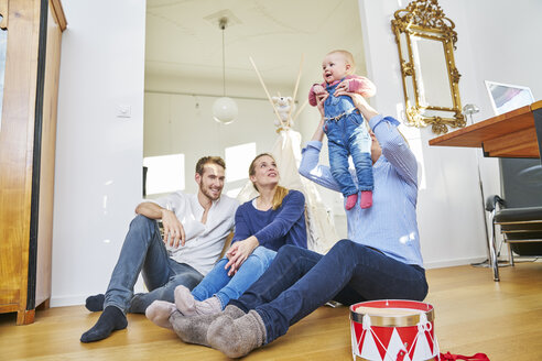 Happy familiy with baby girl playing in living room - FMKF03610