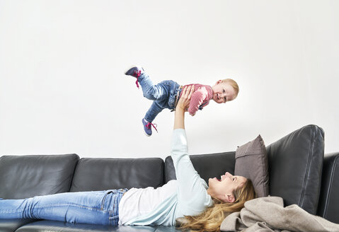 Happy mother lifting up baby girl on couch - FMKF03619