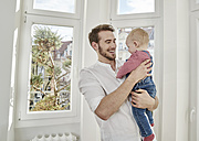 Father holding baby girl at the window - FMKF03622