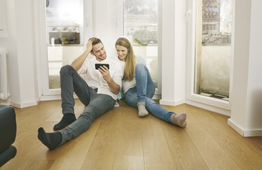 Smiling couple sitting on floor looking at cell phone - FMKF03625
